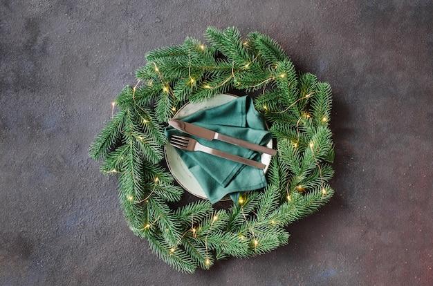 Festosa tavola con decorazioni natalizie a forma di ghirlanda natalizia.