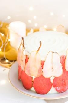 Festosa torta bianca decorata con fette di pera rossa e bianca