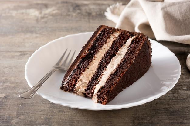 Fetta del dolce di cioccolato sulla tavola di legno