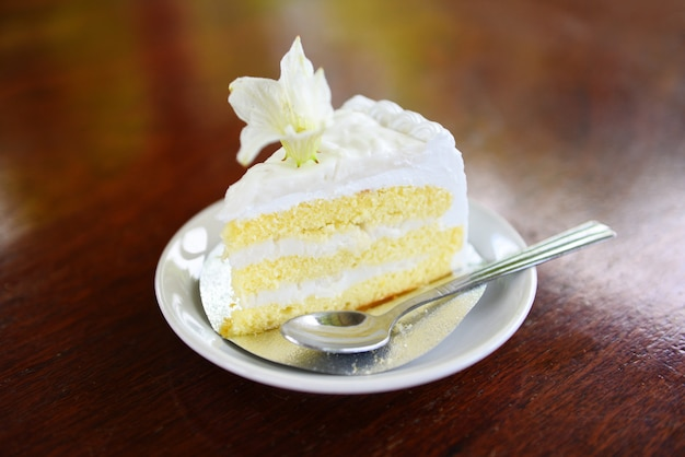 Fetta del dolce su palte bianco con il fiore sul dolce di noce di cocco del fondo di legno della tavola