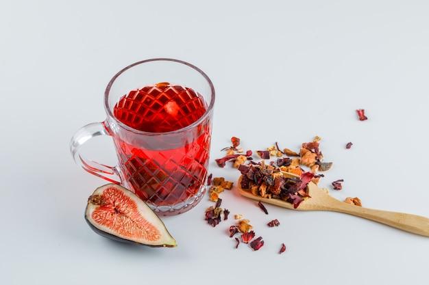 Fetta del fico con la tazza di tè, erbe secche su bianco, vista dell'angolo alto.