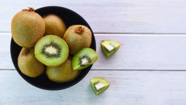 Fetta del kiwi in ciotola kiwi fresco sulla superficie di legno della tavola