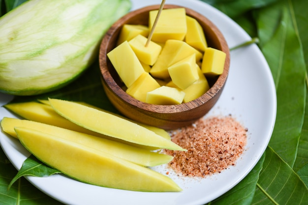 Fetta del mango sul piatto bianco e sulle foglie verdi dal concetto tropicale della frutta di estate dell'albero - mango maturo e manghi verdi per lo spuntino