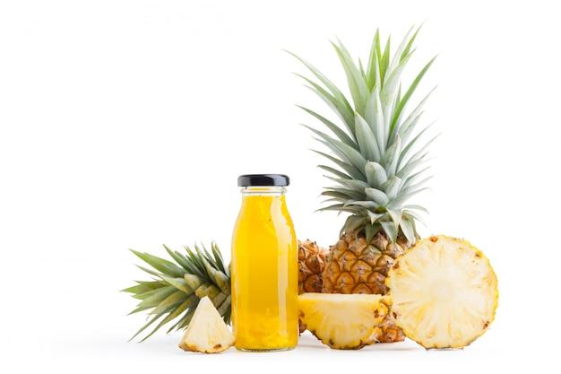 Fetta dell'ananas e succo di ananas in bottiglie di vetro isolate su fondo bianco con il percorso di ritaglio