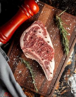 Fetta della carne cruda con sale sullo scrittorio di taglio