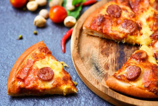 Fetta della pizza sul vassoio di legno e foglia del basilico dei peperoncini rossi del pomodoro sul formaggio tradizionale italiano della pizza degli alimenti a rapida preparazione saporiti deliziosi scuri con la mozzarella