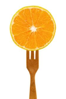 Fetta di arancia fresca sulla forcella su bianco