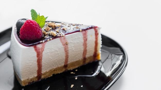 Fetta di cheesecake con salsa di lampone e blu e verde menta sul piatto su sfondo bianco
