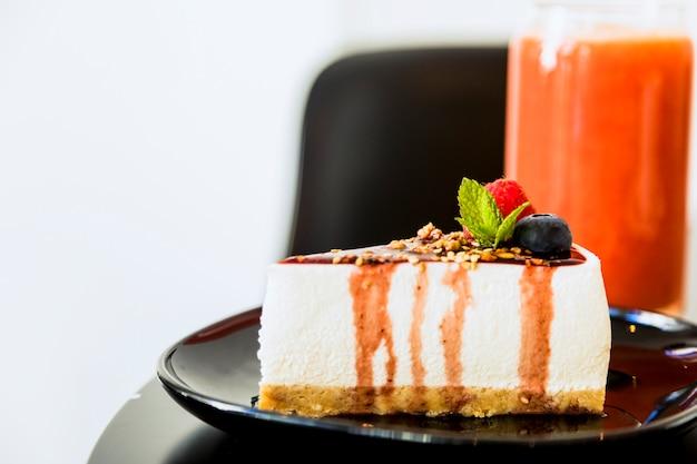 Fetta di cheesecake con salsa e frutti di bosco su piatto in ceramica nera