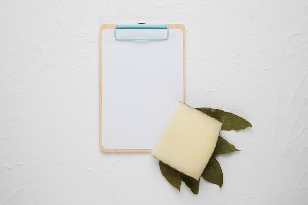 Fetta di formaggio; foglie di alloro secche e appunti su sfondo bianco