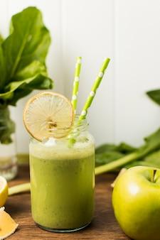 Fetta di frutta vicino a erbe e vetro con cocktail e cannucce