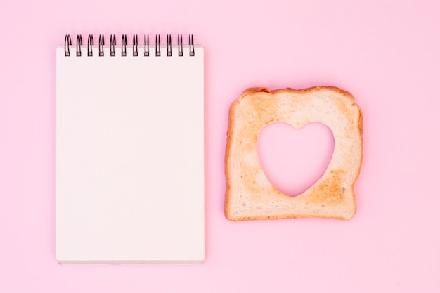 Fetta di pane con cuore tagliato e blocco note