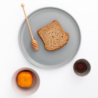 Fetta di pane del primo piano sul piatto con miele