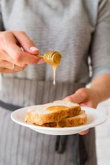 Fetta di pane di versamento del pane ober della donna del primo piano