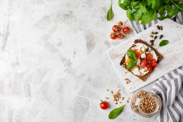 Fetta di pane tostato con pomodorini sul tavolo di marmo copia spazio