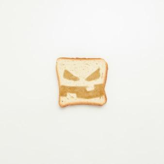 Fetta di pane tostato con un sorriso diabolico su un bianco