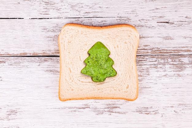 Fetta di pane tostato con una frittata verde a forma di abete, pasto di natale