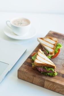 Fetta di panini al prosciutto e tazza di caffè sullo sfondo