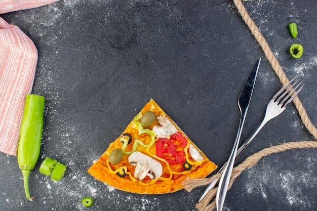 Fetta di pizza ai funghi vista dall'alto con pomodori rossi, olive verdi, funghi su tutto il tavolo grigio, pasta per pizza, carne italiana