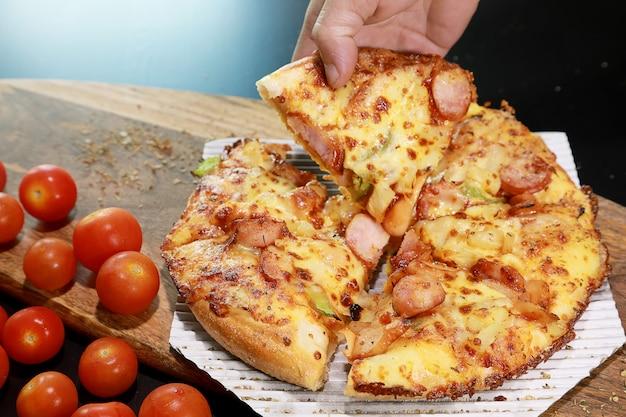 Fetta di pizza calda fatta in casa con la mano dell'uomo e formaggio fuso, salsiccia in cima e pomodoro piccolo.