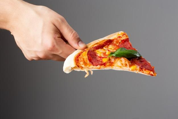 Fetta di pizza casalinga calda deliziosa a disposizione su fondo grigio. pizza - pizza fresca fatta in casa con peperoni, formaggio e salsa di pomodoro, pomodori, mais e basilico con spazio di copia.