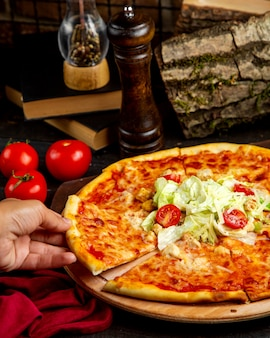 Fetta di pizza con pollo e pomodoro su una tavola di legno