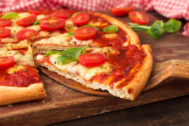 Fetta di pizza deliziosa sulla spatola di legno