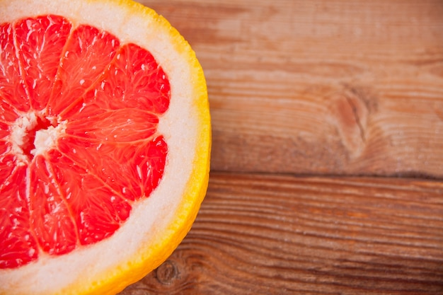 Fetta di pompelmo rosso sul vecchio tavolo