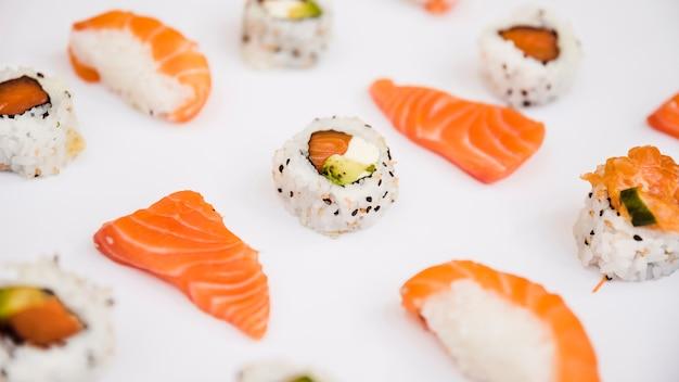 Fetta di salmone e sushi isolato su sfondo bianco
