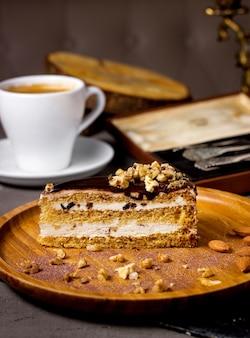 Fetta di torta con topping al cioccolato e noci servito con una tazza di caffè