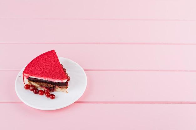 Fetta di torta deliziosa con bacche di ribes rosso sul piatto bianco sopra il contesto rosa della plancia