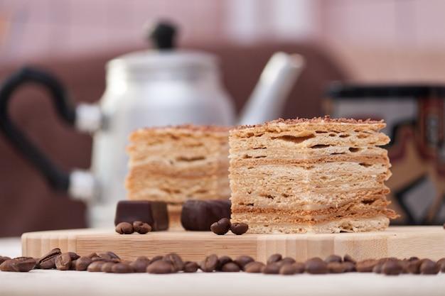 Fetta di torta di miele a strati con chicchi di caffè, caramelle e tazza nera, messa a fuoco selettiva