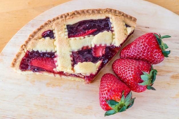 Fetta di torta e fragola fresche di ciliegie fatte in casa sulla tavola di legno