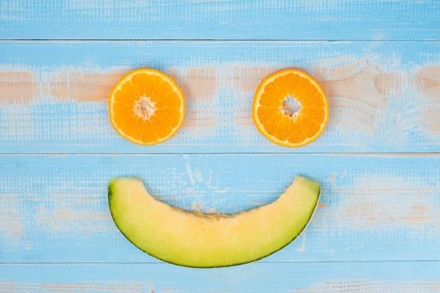 Fetta di vista superiore frutti dell'arancia e del melone dentro sulla tavola di legno blu.