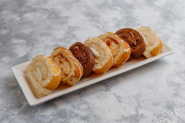 Fetta differente del rotolo del dolce sul piatto ceramico su lihgt con lo spazio della copia