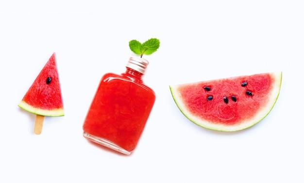 Fetta e ghiacciolo dell'anguria con la bottiglia del succo sano dell'anguria isolata su bianco