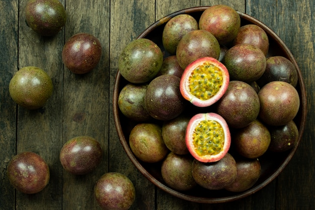 Fetta fresca del frutto della passione in ciotola di legno sulla tavola