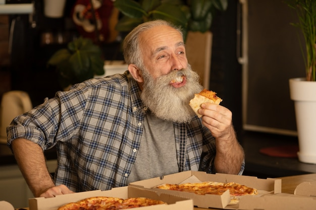 Fetta mangiatrice di uomini sorridente più anziana della pizza che si siede al salone. alimento italiano mangiatore di uomini barbuto senior.