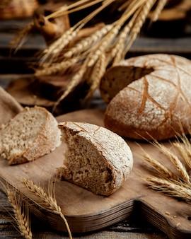 Fetta organica del pane nero disposta sul bordo di legno nello stile rustico
