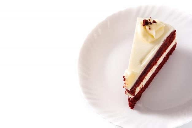 Fetta rossa del dolce del velluto isolata sulla vista bianca e superiore, spazio della copia