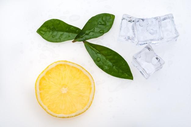 Fetta rotonda di limone luminoso, fresco, succosa e poche foglie verdi e cubetti di ghiaccio su uno sfondo bianco.