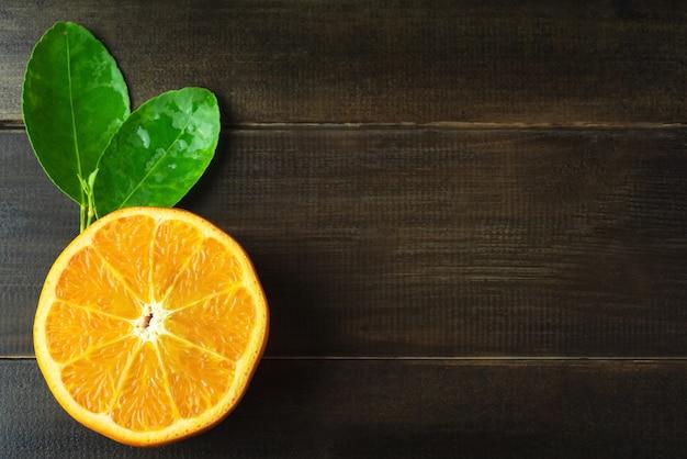 Fetta spremuta d'arancia con foglie su rustico tavolo in legno con spazio per copia, frutta popolare altezza vitamina c e fibra per rinfrescante in estate sapore dolce e acido