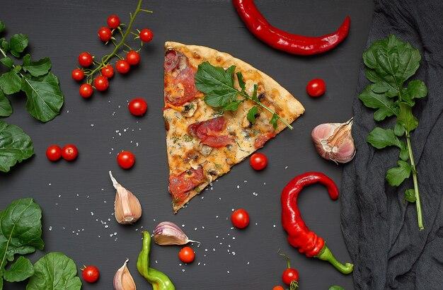 Fetta triangolare di pizza al forno con funghi, salsicce affumicate, pomodori e formaggio, accanto a foglie verdi fresche di rucola