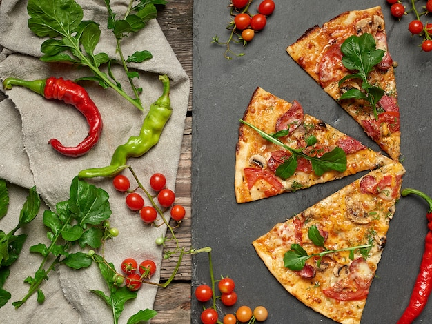 Fetta triangolare di pizza al forno con funghi, salsicce affumicate, pomodori e formaggio