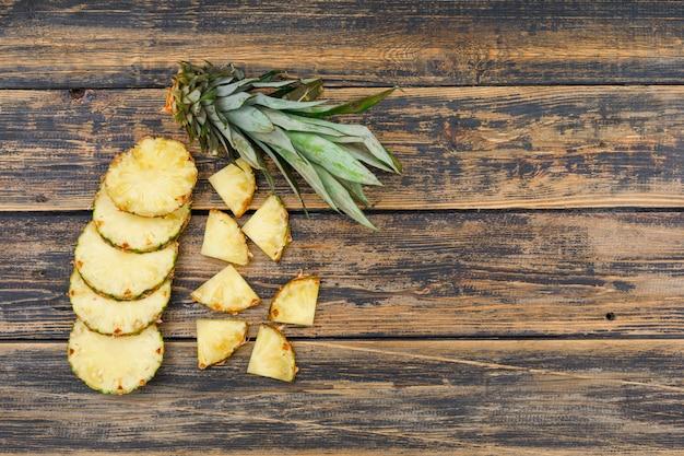 Fette appetitose dell'ananas sul vecchio lerciume di legno. vista dall'alto.