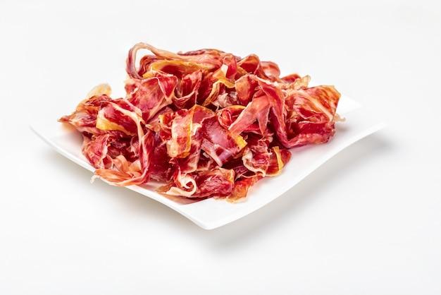Fette appetitose prosciutto iberico su un piatto. carne cruda isolata che diventa un articolo di alta cucina e lusso gastronomico, attraverso un processo di salatura cruda e stagionatura naturale.
