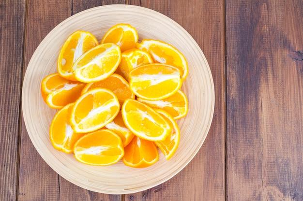 Fette arancio affettate sul piatto di legno.