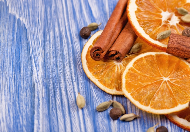 Fette asciutte di arancia, cannella, pimento e cardamomo su una tavola di legno blu