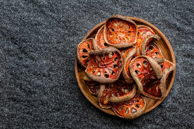 Fette asciutte di baum della frutta di bael (aegle marmelos) in ciotola di legno su fondo nero.