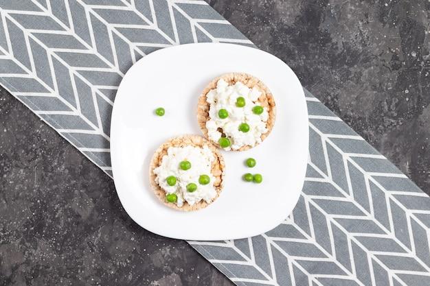 Fette biscottate con ricotta e piselli su un piatto bianco